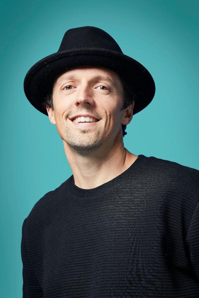 Jason Mraz che sorride con un cappello nero e un maglioncino nero