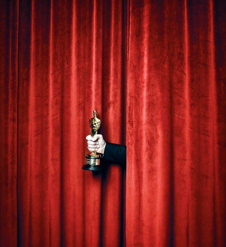 Premio Oscar sbuca da una tenda rossa